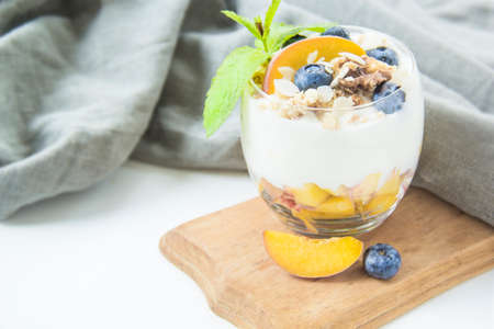 Healthy blueberry, peach and walnut parfait in a glass on a white background Standard-Bild