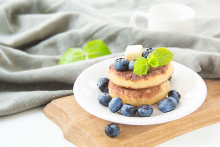 A healthy breakfast of pancakes, berries, butter, and honey