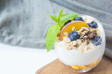Healthy blueberry, peach and walnut parfait in a glass on a white background Reklamní fotografie