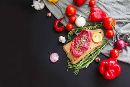 Raw beef steak on a cutting board with spices. Creative atmospheric decoration.
