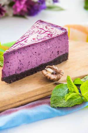 Homemade cheesecake with fresh blueberries and mint for dessert - healthy organic summer dessert pie cheesecake. Creative atmospheric decoration