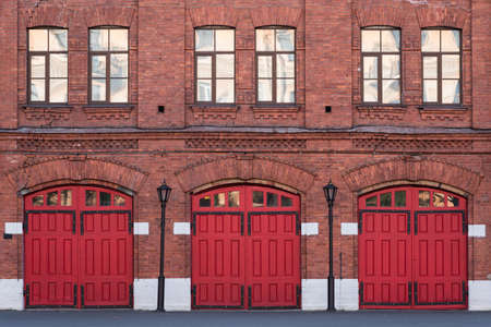 Fire station, an old historic brick building (1880s) with red gates. Fire department in Vasilyevsky Island, St. Petersburg, Russia.