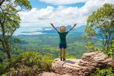 Young traveler in hat stands on rock high in mountains watches beautiful landscape & sea on horizon. View of Ao Nang, bay and islands.