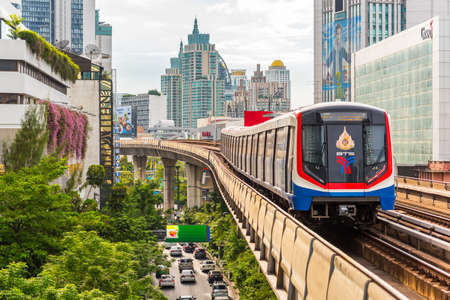 Bangkok - June 25, 2019: a train leaves Nana BTS station, with a view of modern downtown buildings and Sukhumvit Road.