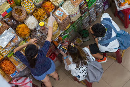 Danang, Vietnam - October 14, 2018: young woman traveler, accompanied by a man, counts expenses on calculator while a seller points with a finger at one of the products at a grocery in Cho Han market. Stock fotó - 154545783