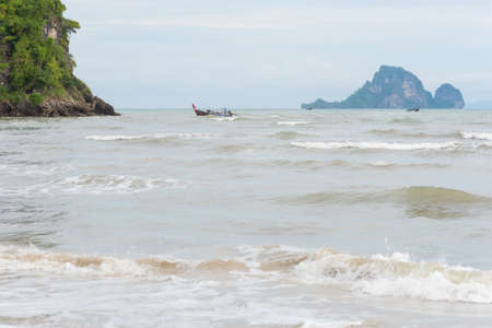 Sea at Ao Nang Beach during the windy overcast day in the low season. Longtail boats and an island in the distance. July in Krabi, Thailand.