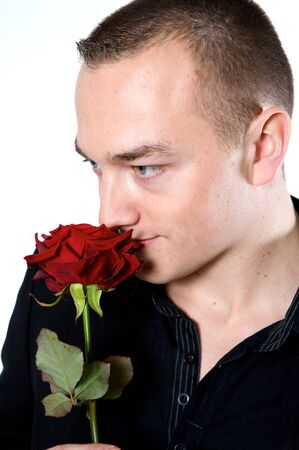 man smelling a rose on a with background