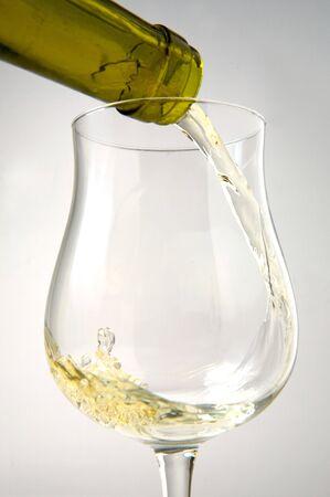 white wine and glass mouvement liquidon a white background