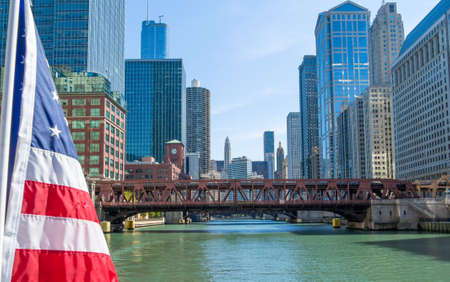 Daytime view of chicago river downtown from a boat with american flag in foreground photo