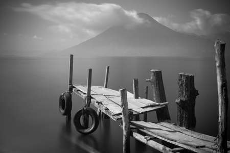 rickety: Old rickety wooden pier juts out into lake Atitlan  Guatemala  with volcano in background   Black and White