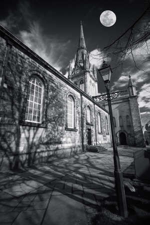 shadowy: Gothic church in shadowy black and white with moon above - composite Stock Photo