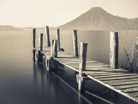 old pier: An old wooden pier juts out into lake Atitlan in Guatemala with volcano in background