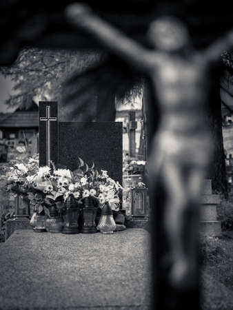adjacent: Blank black granite gravestone in black and white, with adjacent flowers and out of focus crucifix in foreground