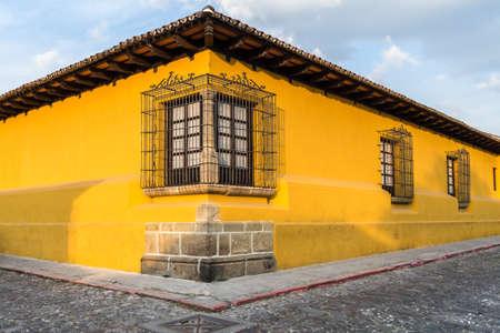 casa colonial: Perspectiva de la esquina de una casa colonial de color amarillo brillante con ventanas enrejadas en Antigua, Guatemala