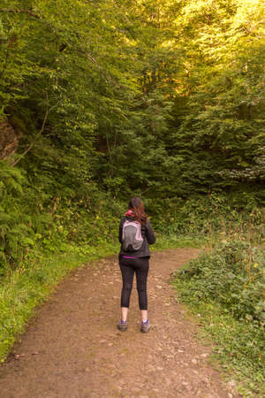 young woman hiking in mountain forest