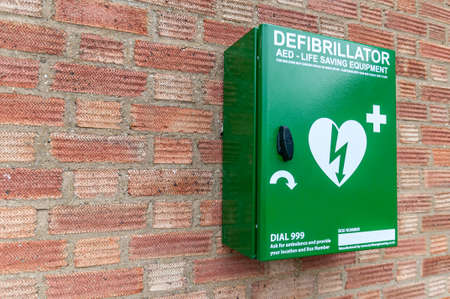 Emergency defibrillator mounted on a brick wall for public use.