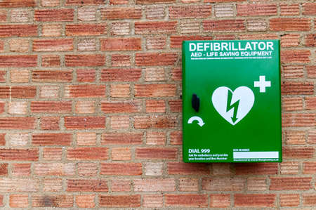Emergency defibrillator mounted on a brick wall for public use.