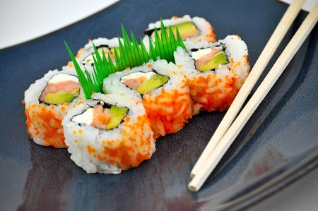 Sushi California or Philly rolls appetizer with rice, avocado, and salmon served on a blue dinner plate with chopsticks.