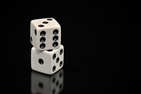 Two white dice stacked on top of each other and isolated on a black background with a soft reflection underneath. Plenty space for ad copy.