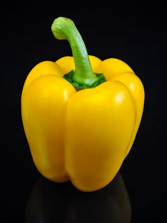 Fancy yellow bell pepper vegetable with green stem isolated on a solid black background.