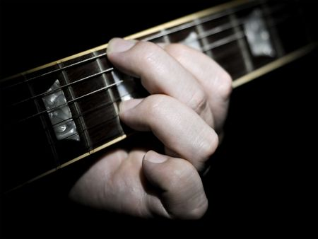 inlays: Guitar player with fingers on the fretboard fingering a chord with a black background. The guitar neck fretboard has mother of pearl or abalone inlays.