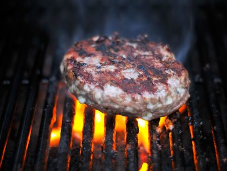 Flame Broiled Juicy Bleu Cheese Hamburger Smoking On The Gas BBQ Grill Stock Photo - 3528866