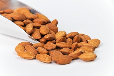 allergens: Fresh Raw Almonds in Aluminum Scoop Isolated on White Background.  Nuts are spilling out on solid bg with plenty of room for ad copy. Stock Photo