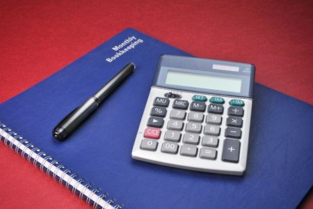 Business Books, Calculator, Expenses, Bookkeeping, Pen on top of blue spiral bound monthly accounting income and expense reports with deep red background.