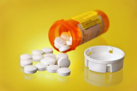 Spilled Prescription Medication w Orange Pill Bottle and cap on solid yellow gradient background Banco de Imagens