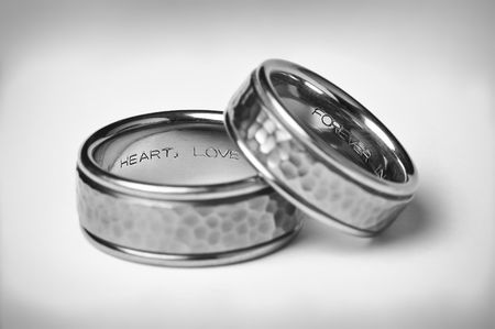 Two Titanium Silver Wedding Bands with heart, love, and forever inscriptions on a soft white gradient background with vignette symbolizing marriage.