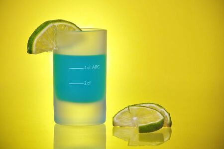 Shot Glass With Blue Tequila Liquor Shooter and Lime Slices on a yellow gradient background