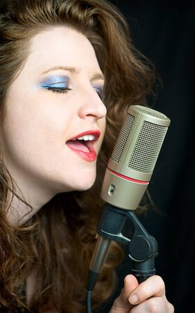 Pretty Woman Singing Into Microphone With Red Lipstick Stock Photo