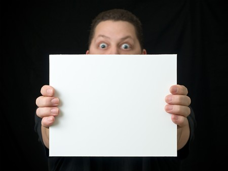 Guy Holding Blank Sign or Paper on solid black background with eyes wide open expression