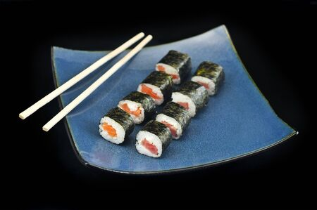 Sushi Philly rolls appetizer wrapped with rice, tuna, and salmon on square blue plate w chopsticks Stock Photo