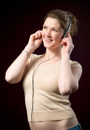 Beautiful Smiling Redhead Girl Wearing Music Headphones isolated on dark background photo