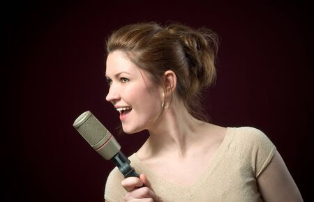Beautiful Redhead Model Singing into Gold Microphone on deep red background