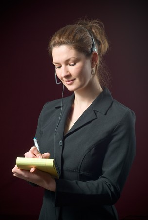 dictating: Beautiful Secretary Wearing Headset Taking Dictating Notes on yellow notepad with a dark background