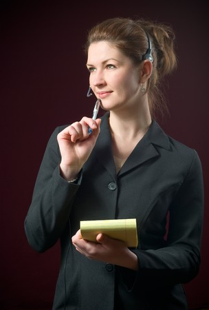 Beautiful Secretary Wearing Headset Taking Dictating Notes on yellow notepad with a dark background Stock Photo - 4292125