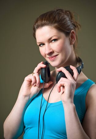 Beautiful Smiling Redhead Girl Wearing Music Headphones with blue tank top shirt holding around neck