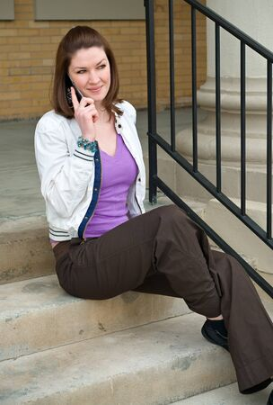 Pretty Young Brunette Model Talking On Cell Phone while sitting on concrete steps outdoors Stock Photo