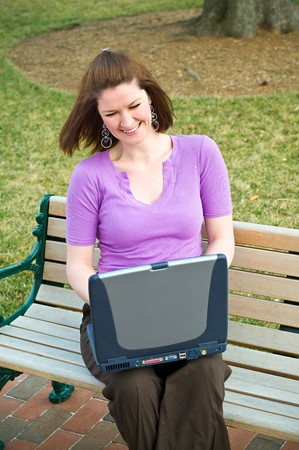 Laughing Young Student Girl Using Wireless Internet Laptop Technology and laughing on a park bench Stock Photo