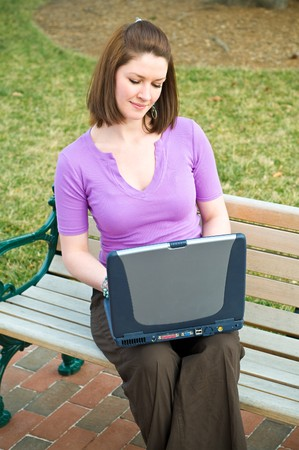Pretty Young Student Girl Using Wireless Internet Laptop Technology on a park bench