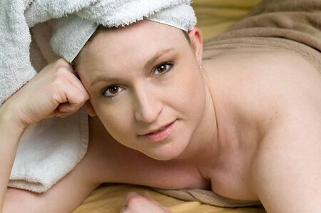 towel wrapped: Beautiful Salon Woman Relaxing at Spa smiling with white towel wrapped head laying on gold silk