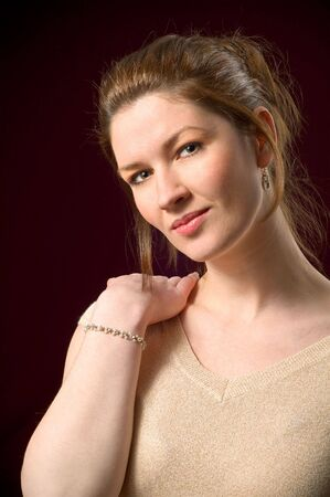 Attractive Female Portrait Modeling in Studio on Dark Red Background posing holding hand on shoulder Stock Photo