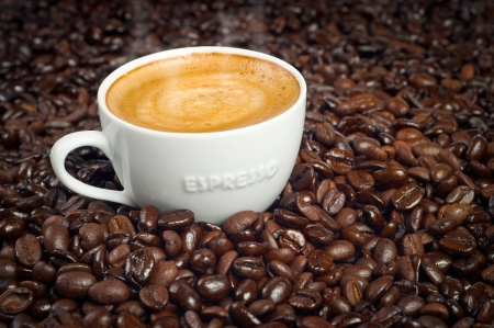 Cup of Morning Espresso in Dark Roasted Coffee Beans background steaming with frothy crema on top Stock Photo