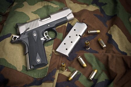 45 caliber: 45 Firearm Pistol Clip And Hand Gun Ammunition on military camouflage background
