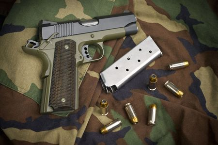 45 gun: 45 Firearm Pistol Clip And Hand Gun Ammunition on military camouflage background