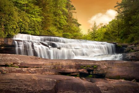 Motion Blur Waterfalls Nature Landscape in Blue Ridge Mountains Sunset with green trees, rusty natural orange rocks and flowing water Stock Photo