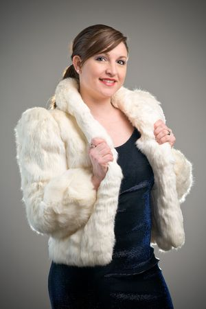 Fashion and glamour image featuring woman model modeling a white fur jacket and blue dress Stock Photo