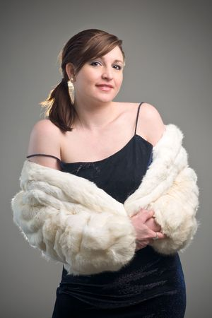 Fashion and glamor image featuring woman model modeling a white fur jacket and blue dress
